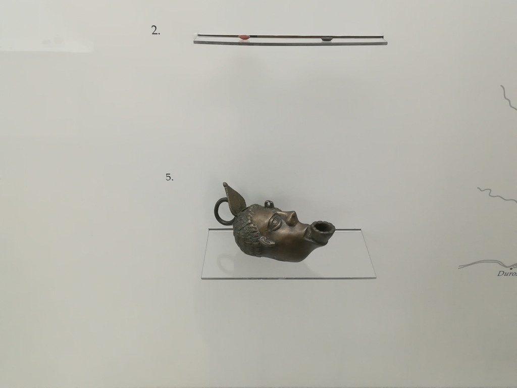 opaitul din metal cu cap de om si cele de lut cu un leu in relief.